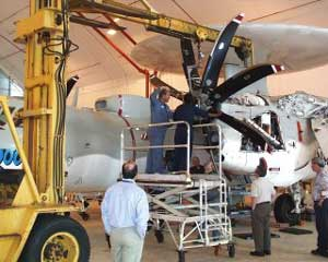 Photo of the E-2C Hawkeye 2000 in a hangar having the propeller worked on